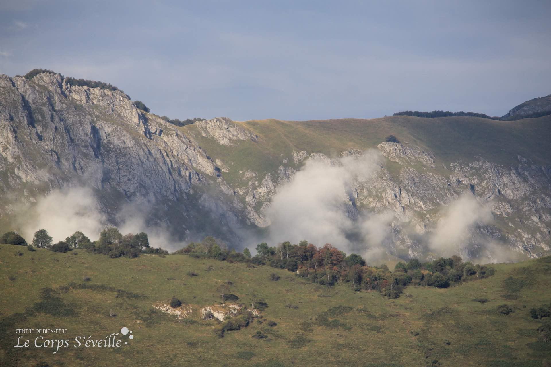 Les nuages surfent sur les crêtes en montagne, en Pyrénées béarnaises. Randonner les pieds sur terre.