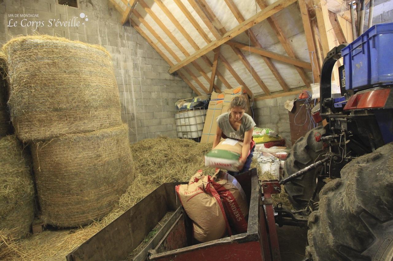 Laura charge un sac de granulés dans le local à nourrissage.