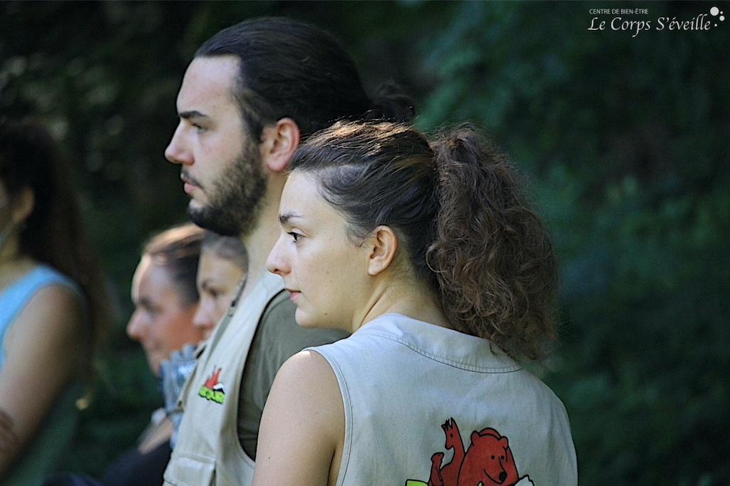 Djanisse, Rémi et Laura, accompagnés de stagiaires, observent les ours Diego et Ségolène après avoir nettoyé l'enclos puis caché la nourriture pour stimuler les animaux. Parc Ours, refuge et parc animalier en Pyrénées béarnaises.